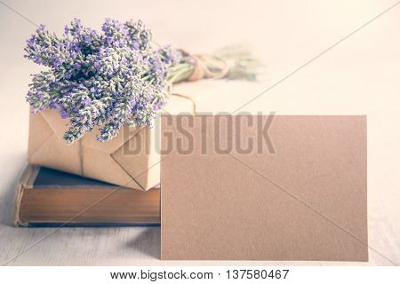 Empty greeting kraft card in front of a lavender bouquet wrapped gift and old book over a white wood background. Vintage style.