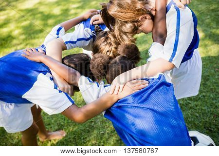 Overhead view of soccer team forming huddle in the park