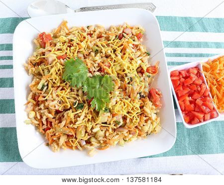 Bhel puri, an Indian popular street food, made from puffed rice and items like tomato, onion, carrot and cucumber.