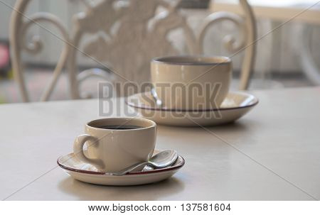 Two coffee cups stand on a table (monochrome)
