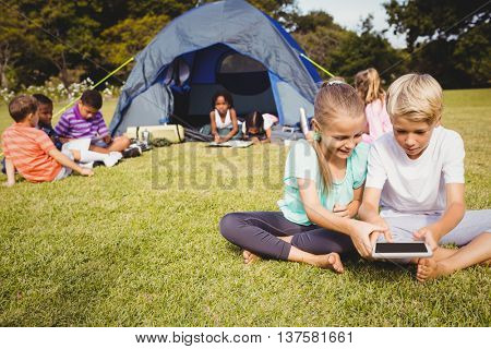 Smiling children are looking their tablet with other children behind them at park