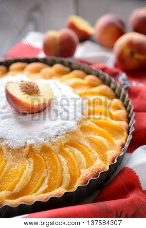 Fresh peach pie sprinkled with sugar on wooden background