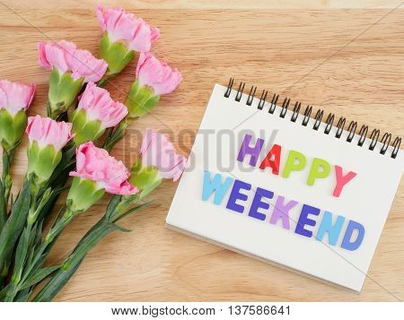 Word spell Happy Weekend on notebook and bouquet of sweet pink Carnation flower on wood background with top view