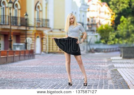 Beautiful blonde woman at the colorful summer city in the striped t-shirt posing on the street with her skirt- photo with shallow dept of field