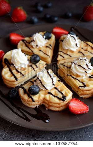 Waffles with blueberries, strawberries, whipped cream and chocolate sauce