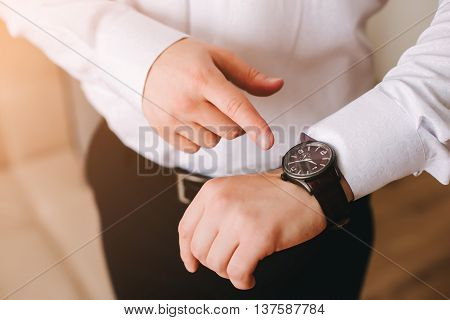 businessman in white shirt looking at his swiss wristwatch on his hand and watching the time.