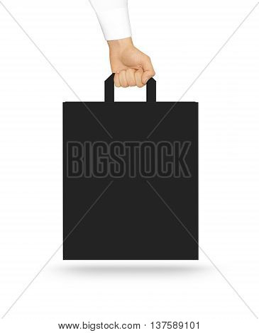 Blank black paper bag mock up holding in hand. Consumer pack ready for logo design or identity presentation.