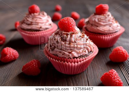 Raspberry cupcakes sprinkled with chocolate on dark background