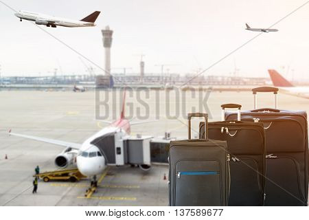 Closeup of group of luggage with the blurred of the airport runway background.