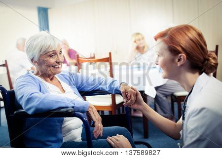 Nurse interacting with a senior woman in wheelchair in the retirement house