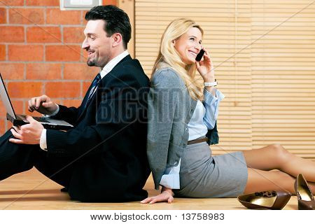 Couple �¢�?�? businesswoman and businessman �¢�?�? working at home sitting on the floor