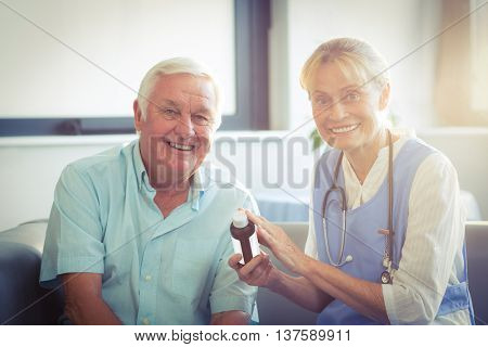 Female doctor giving medicine to senior man after meal