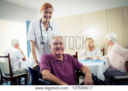 Portrait of a nurse with senior man in wheelchair in the retirement house