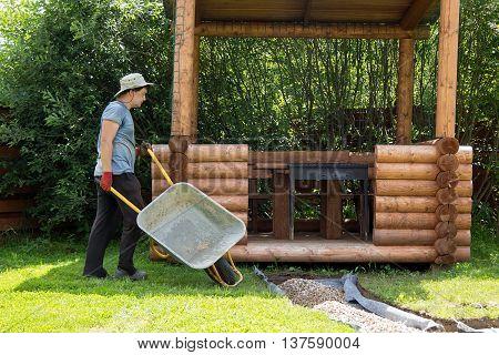 Man Carries Gravel For Paths In Wheelbarrow