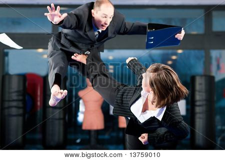 Business concept - People in a gym in martial arts training exercising Taekwondo, both wearing suits