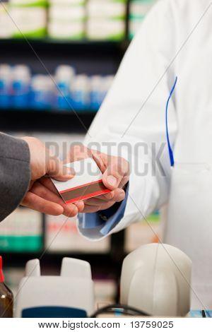 Apotheker mit Kunden in der Apotheke; der Kunde zahlt mit Kreditkarte; von beiden nur die Hände ein