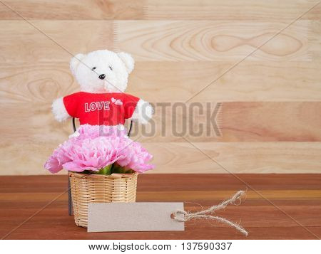Brown blank label bouquet pink Carnation flower and teddy bear on wood background (Love Concept)