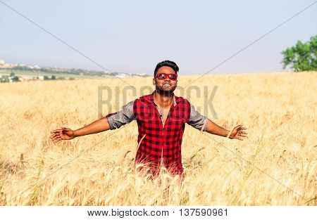 Young indian man walking in wheat field - African american guy open arms at sky through a corn field - Asian farmer with open arms towards the sun - Concept of freedom and joy for successful achieved