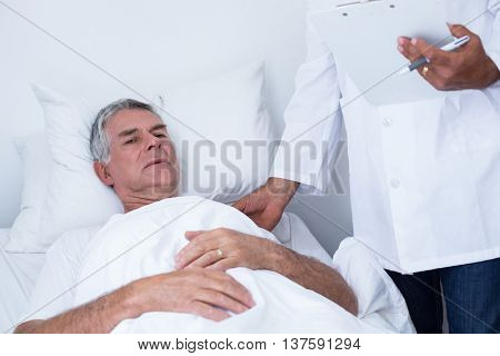 Male doctor examining senior man in hospital