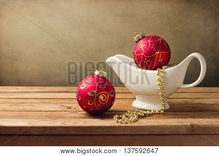 Christmas background with ornaments and gravy boat on wooden table