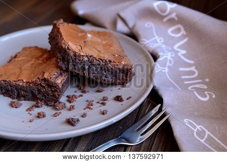 Chocolate brownies on a gray plate and wooden background