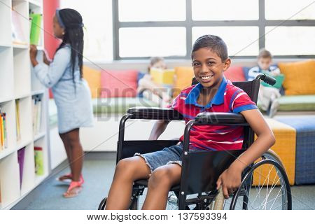 Portrait of disabled schoolboy on wheelchair in library at school