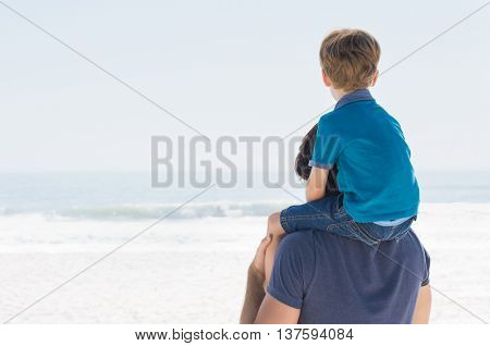 Little boy enjoying sea view sitting on father shoulder. Son sitting on father shoulder and looking the sea. Vision and future concept.