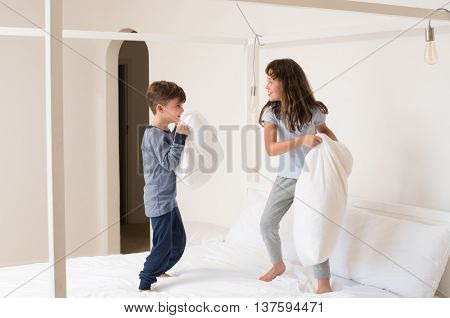 Siblings fighting using pillow in bedroom. Happy laughing brother and sister having a pillow fight in bedroom. Kids playing with pillows on parent bed.