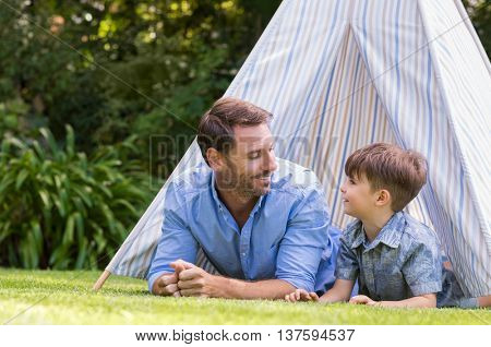 Father and son lying with their head outside the tent. Smiling man and happy cute boy playing the indians with the tent in a garden.. Man enjoying listening to the boy.