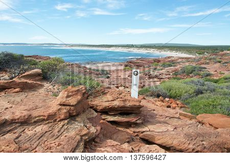 Sandstone rock formations line the Red Bluff trail with native flora overlooking the turquoise Indian Ocean bay under a blue sky in Kalbarri, Western Australia.