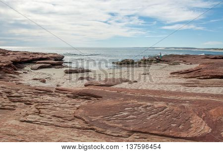 Red Bluff beach with red sandstone and the Indian Ocean seascape under a cloudy sky on the coral coast in Kalbarri, Western Australia.