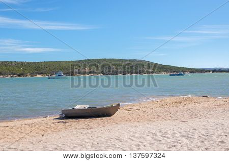 Beached dingy on the sandy bank of the coastal Murchison River with vegetated dunes under a blue sky in Kalbarri, Western Australia.