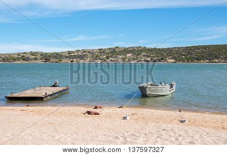 Dingy and platform boat floating by the sandy beach along the peaceful Murchison River with coastal dunes under a blue sky in Kalbarri, Western Australia.