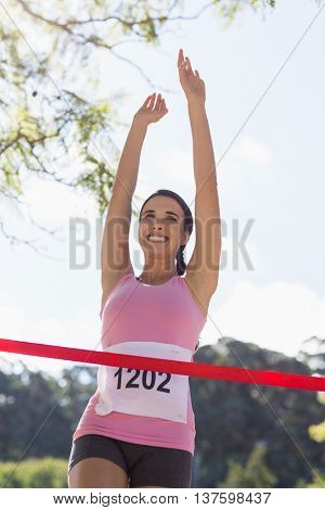 Cheerful winner female athlete crossing finish line in park