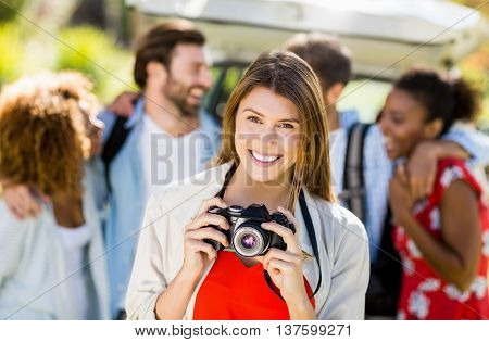 Portrait of beautiful woman clicking a photo from camera in park on sunny day
