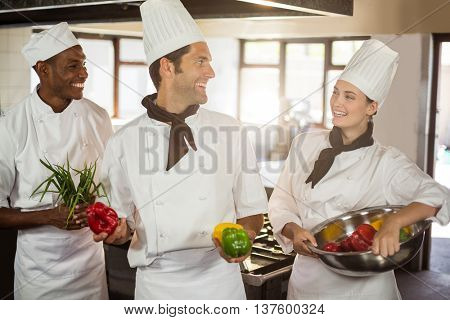 Smiling three chefs holding a vegetables in commercial kitchen