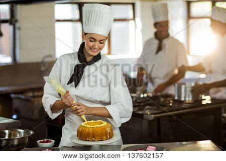 Female chef piping icing on cake in a commercial kitchen