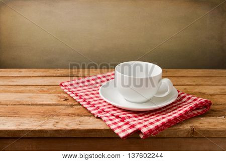 Empty coffee cup on tablecloth on wooden table over grunge background
