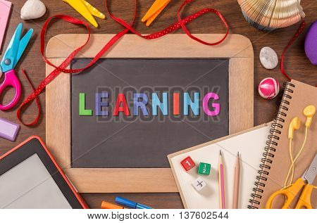 Learning word formed by wooden color alphabets on small blackboard surrounded by school supplies on wooden table