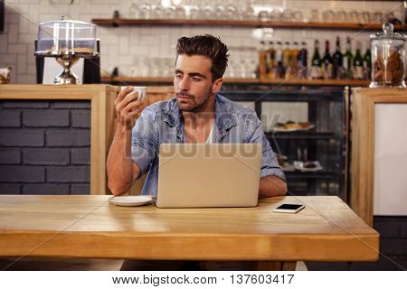 Portrait of hipster man sipping coffee at cafe