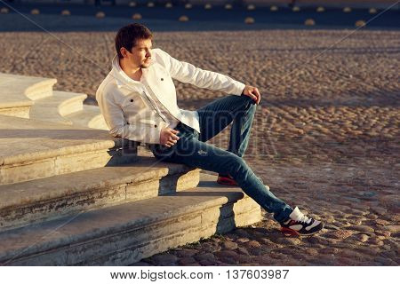 Young stylish man sitting on stairs outdoors on a summer evening. fashion stylish portrait
