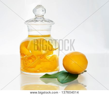 a glass jar with lemon zest inside next to a fresh lemon with green leaf. limoncello liqueur