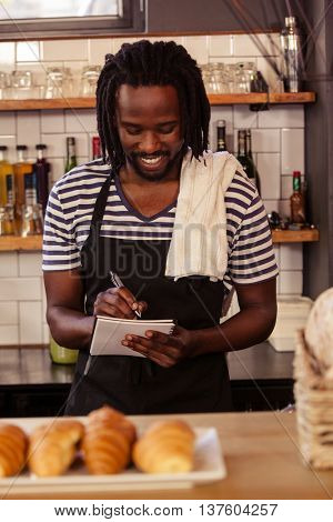 Portrait of smiling hipster taking an order at work at coffee shop