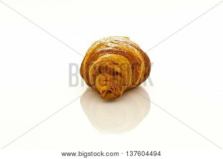 Croissant with powdered sugar with reflection on white background.