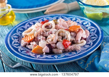 A delicious mixed seafood salad with octopus calamari shrimp onions red pepper and carrot.