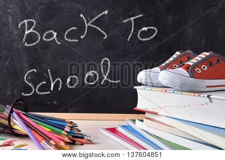 Back To School Written On Blackboard And Tools Front
