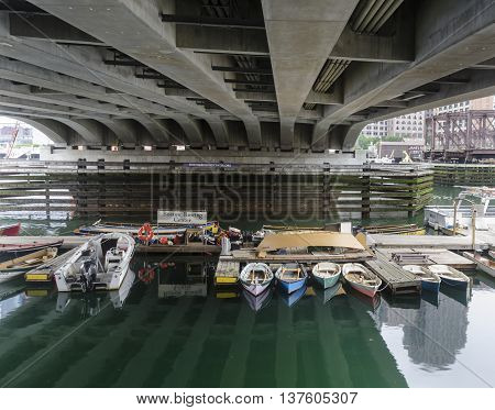 BOSTON MASSACHUSETTS USA - July 7 2016: Variety of rowing craft waiting to be put to use at Boston Rowing Center on Fort Point Channel under Seaport Blvd. in South Boston