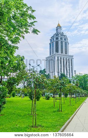 The modern clock tower is seen through the greenery of Batumi Boulevard Georgia.