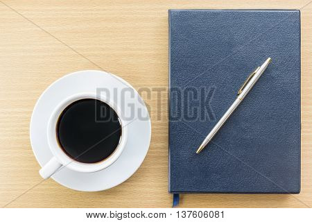 Coffee And Notebook On Wood Table