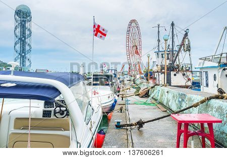 The moored yachts and fishing trawlers in Batumi port with the ferris wheel on the background Georgia.